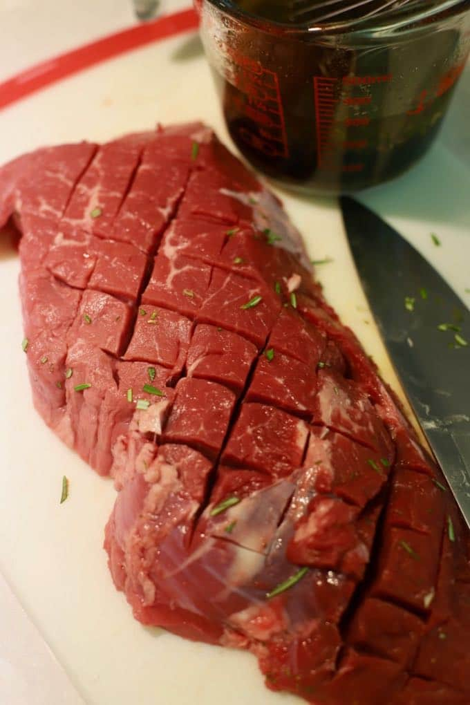 A raw steak on a cutting board with shallow criss cross cuts across it.