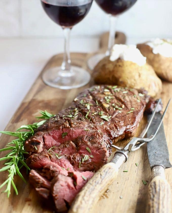 A grilled steak on a cutting board along with baked potatoes and two glasses of wine.