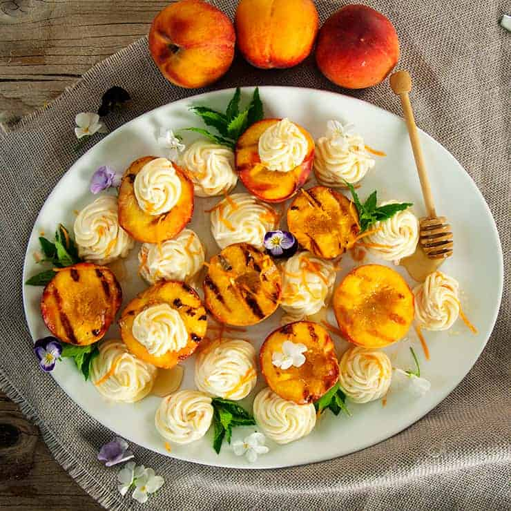 A white plate with grilled peaches.