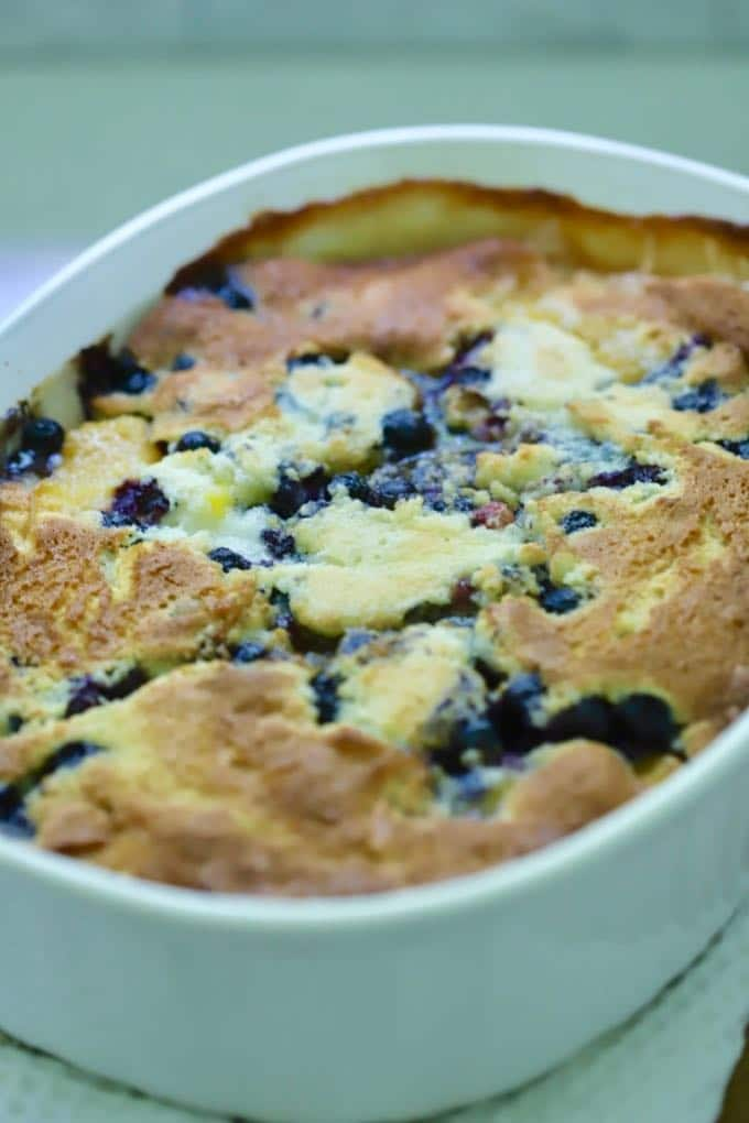 Blueberries and peach cobbler in a white baking dish right out of the oven.