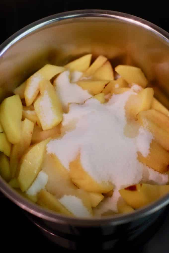 Sliced fresh peaches in a saucepan topped with granulated sugar.