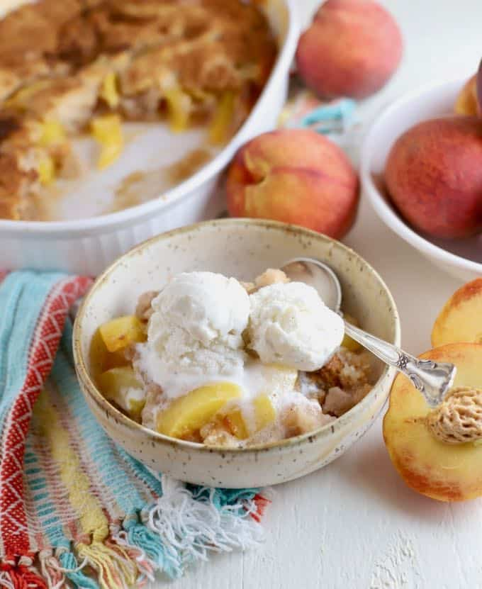 Peach Cobbler in a bowl with two scoops of ice cream on top.