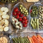 Seven glass relish trays with an assortment of marinated and pickled vegetables.