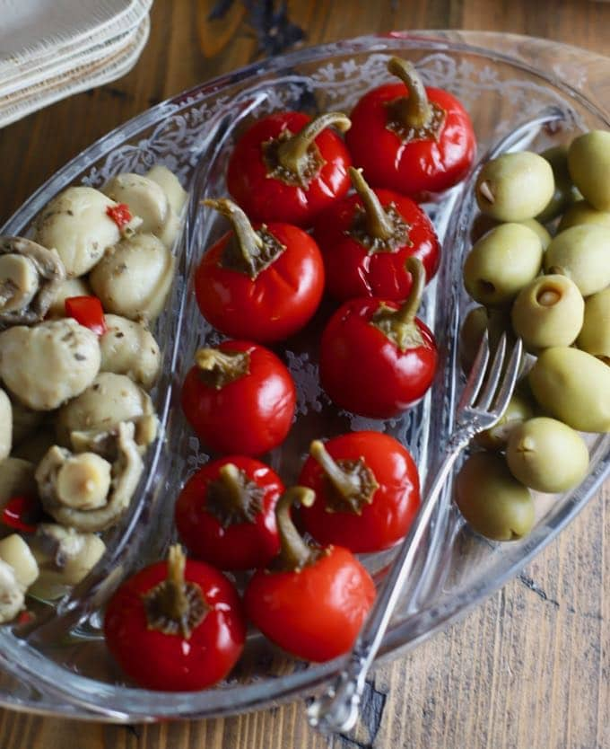 A glass dish with mushrooms, spicy cherry peppers and stuffed olives.