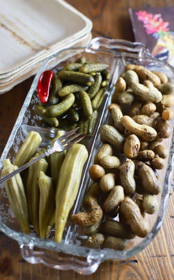 A glass dish with pickled okra, boiled peanuts and gherkins.