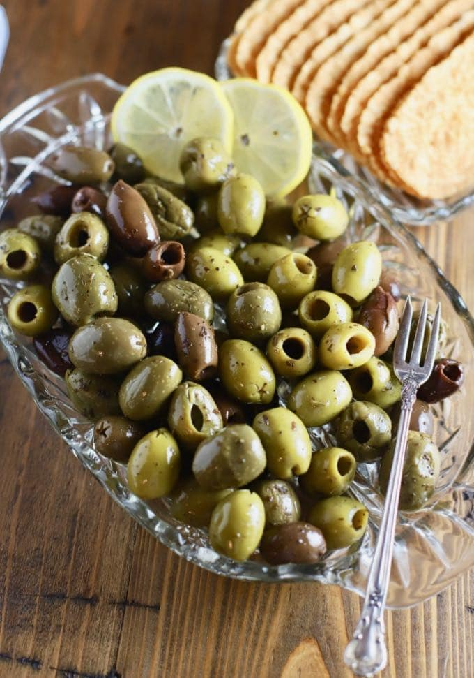 Mixed green and black olives on a glass dish garnished with lemon slices.