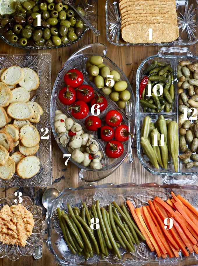Seven glass trays on a board filled with relish tray items like olives and pickles.