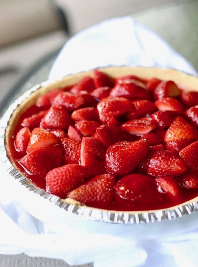 Whole fresh Strawberry Pie on a white cloth napkin