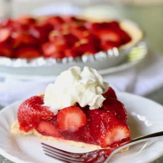 A slice of strawberry pie topped with whipped cream on a plate with a fork.