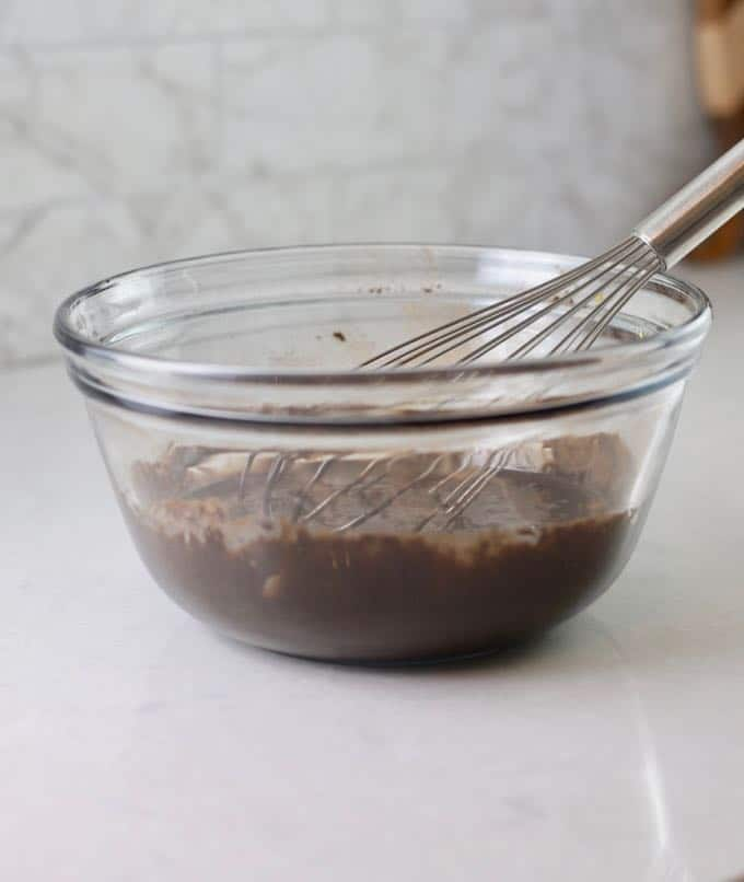 Cocoa powder and sweetened condensed milk in a glass mixing bowl with a whisk.