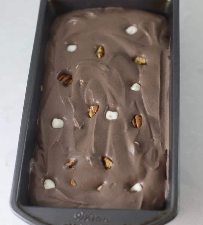 A metal loaf pan with chocolate ice cream, marshmallows and nuts ready for the freezer.