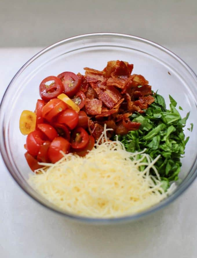A clear glass bowl with sliced cherry tomatoes, chopped spinach, shredded cheese and crumbled bacon.