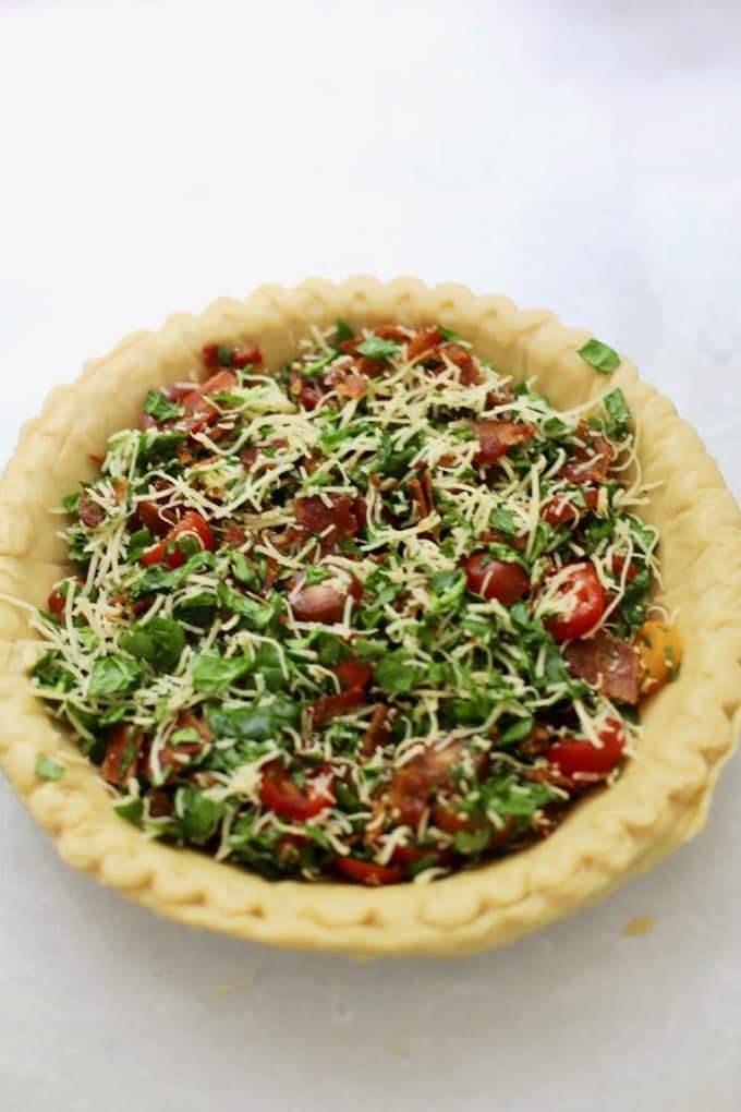 A pie crust with spinach, tomatoes, and cheese.
