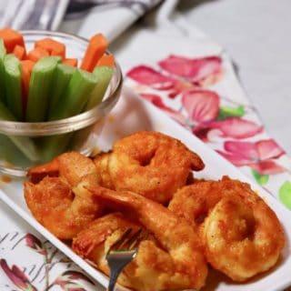 A white plate with buffalo shrimp, carrots and celery.
