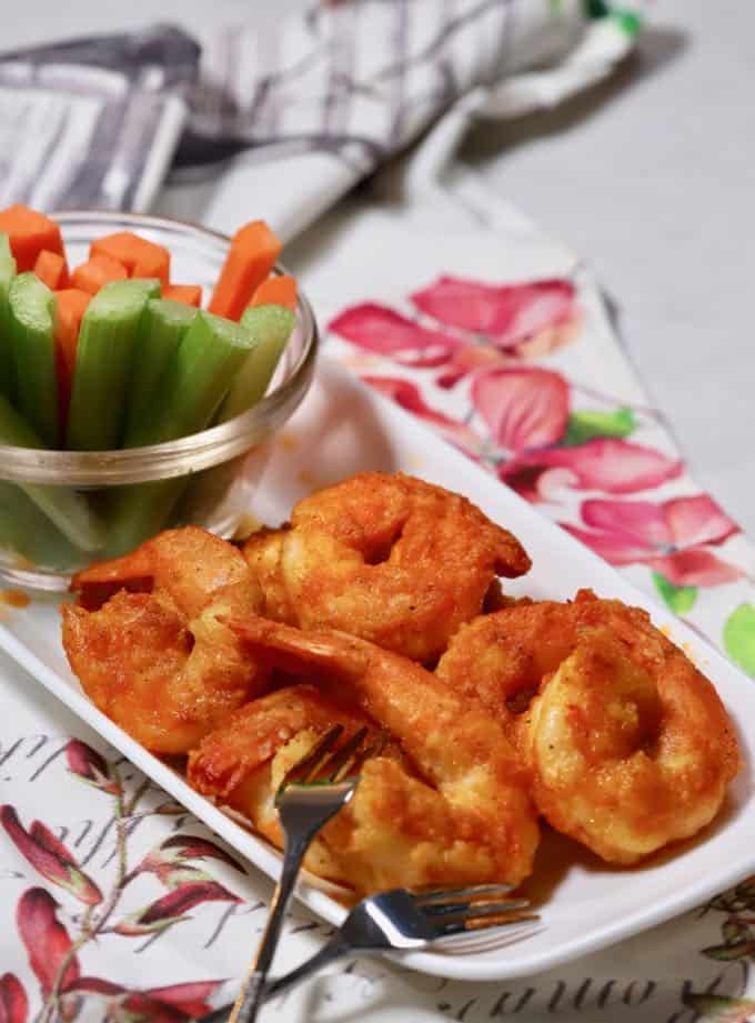 A white plate with buffalo shrimp, carrots and celery.
