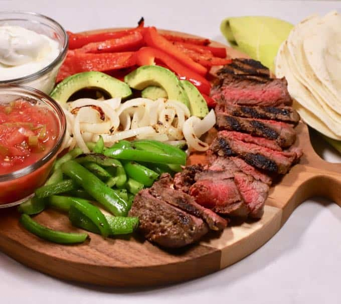 Grilled Steak Fajita ingredients on a wooden cutting board.