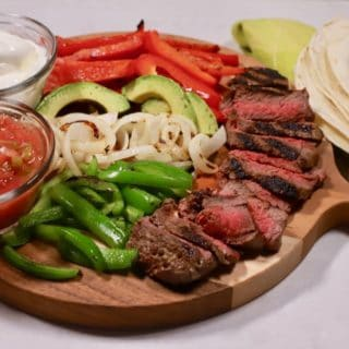Fajita ingredients on a cutting board including steak, peppers, onions, and tortillas.