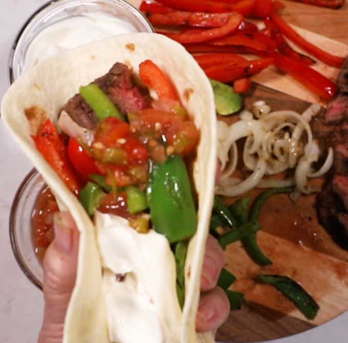 Steak fajita full of strips of steak, peppers and onions.