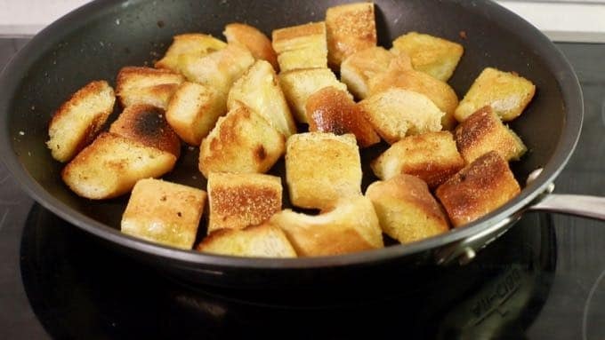 Large cubes of bread toasting in a saute pan.