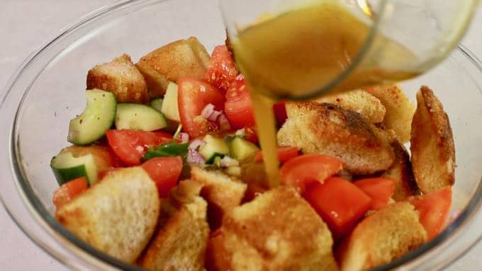 Adding dressing to panzanella salad in a clear glass bowl.