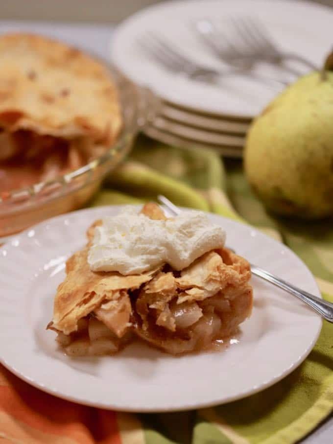 A piece of pear pie topped with whipped cream on a white plate.