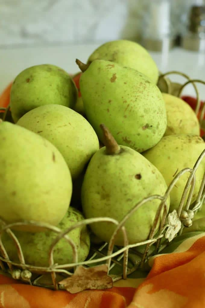 A basket of pears on a kitchen counter.