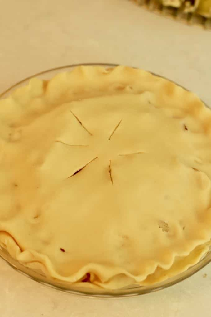 An unbaked pear pie with a top crust ready for the oven.