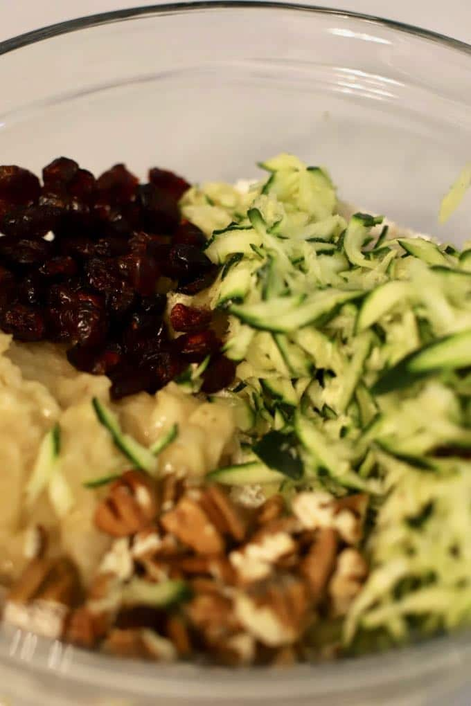 A clear glass bowl with grated zucchini, pecans, craisins and a mashed banana.
