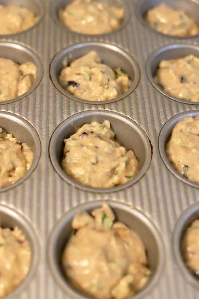 Zucchini Banana Muffin batter in a 12 cup muffin pan.