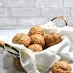 Zucchini Banana Muffins in a basket on a kitchen counter.