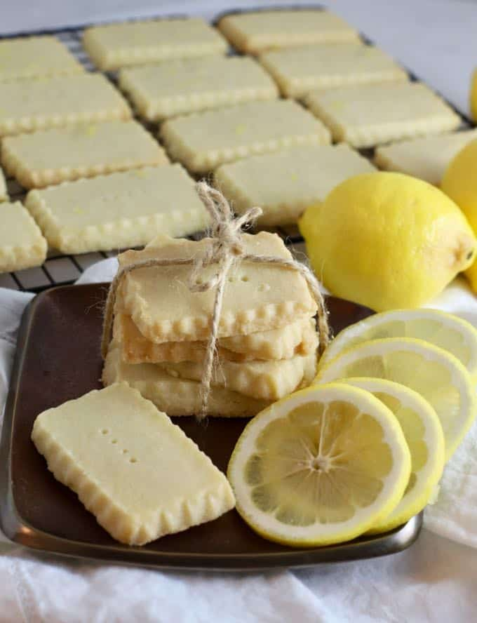 A stack of lemon shortbread cookies tied with a piece of string and lemon slices on a plate.