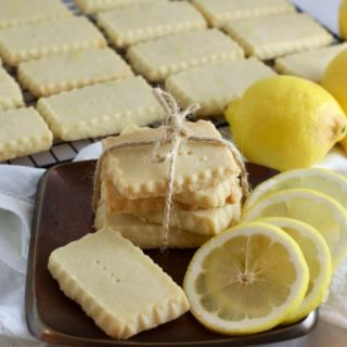 Lemon shortbread cookies on a bronze metal plate with lemon slices.