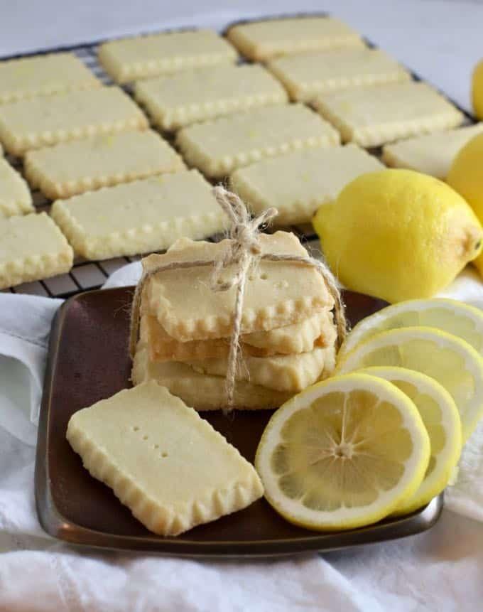 Lemon shortbread cookies on a bronze metal plate with lemon slices.