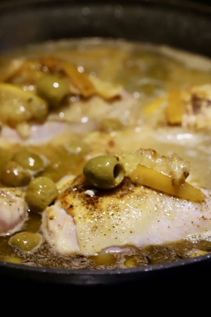 Chicken, olives, pasta and lemons in a skillet cooking.