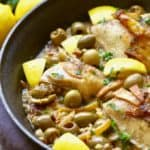 Chicken, lemons, olives and pasta in a skillet for Mediterranean Chicken Bake.