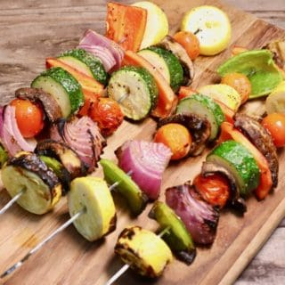 Four grilled veggie skewers on a wooden cutting board.