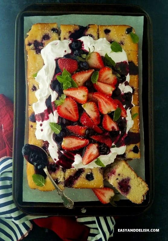 Easy and Delish Berry Cake topped with strawberries and blueberries.