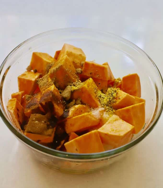 Sweet potato cubes with olive oil and seasonings before roasting.