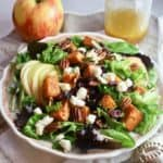 A large bowl with lettuce, sweet potatoes, apples, croutons and pecans for a Fall harvest salad.