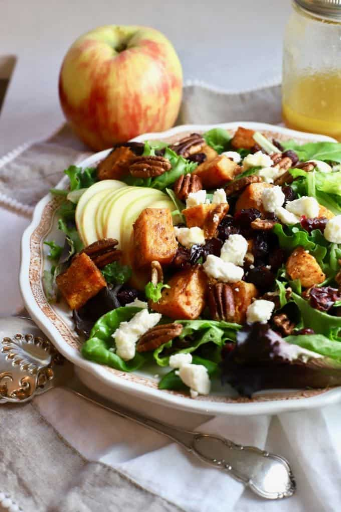 Fall Harvest Salad in a large white bowl with an apple in the background.