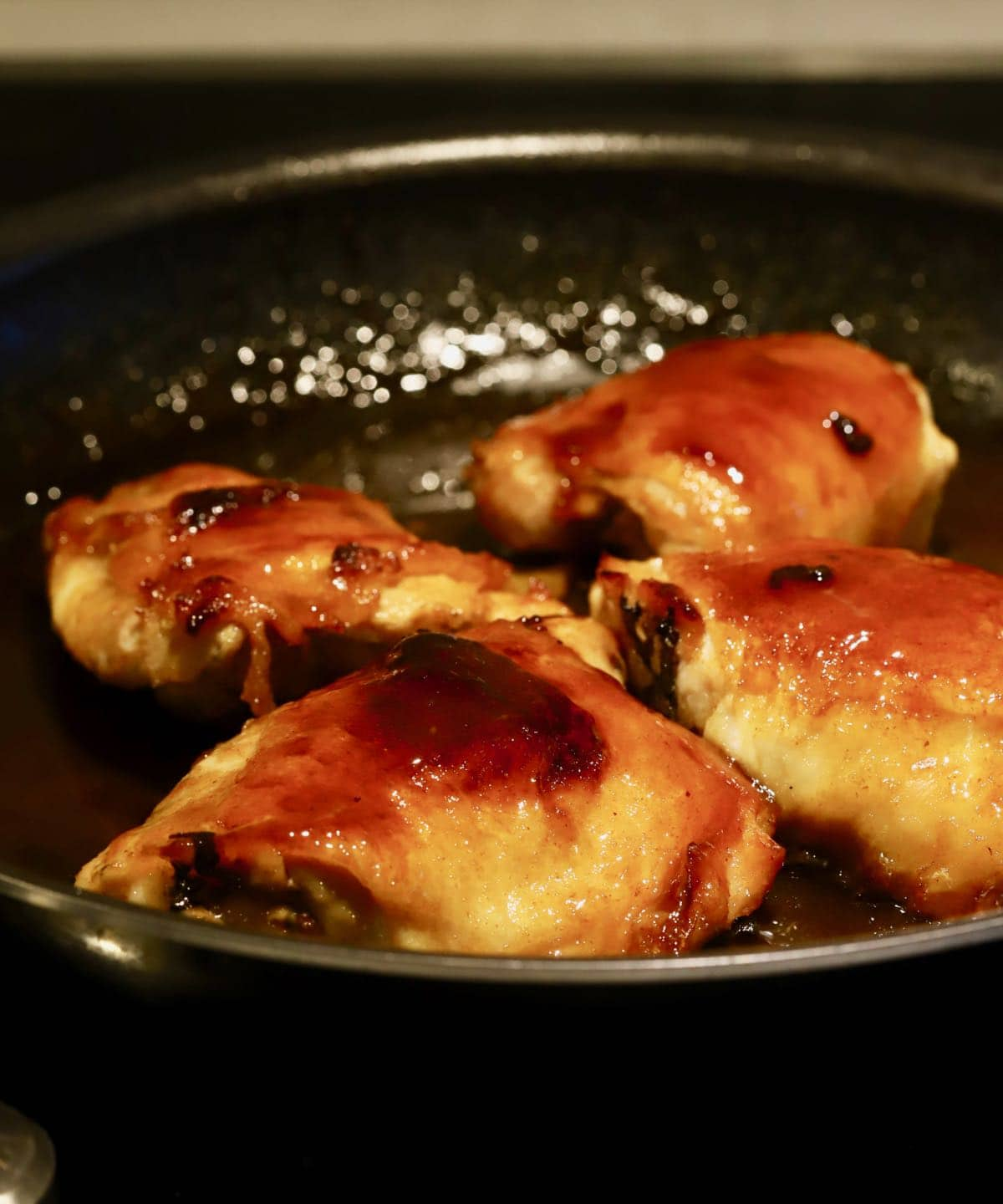 Four chicken thighs being pan-seared in a skillet.