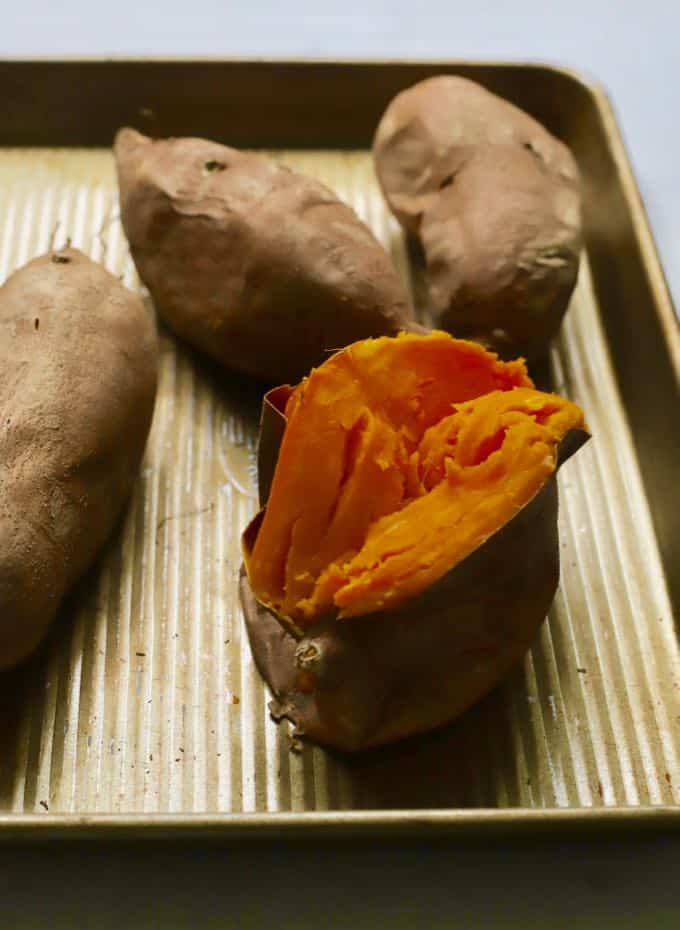 Baked sweet potatoes on a baking sheet with one cut in half.