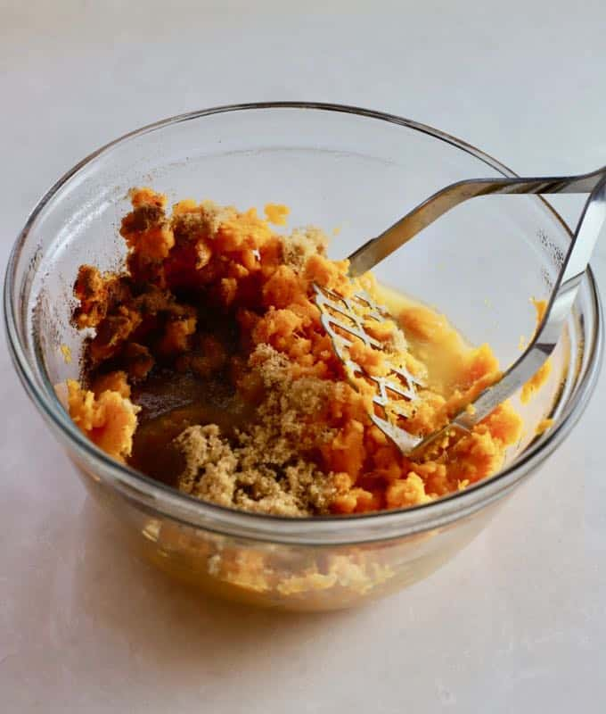 Sweet potatoes, brown sugar, butter, and spices for sweet potato casserole in a glass bowl.