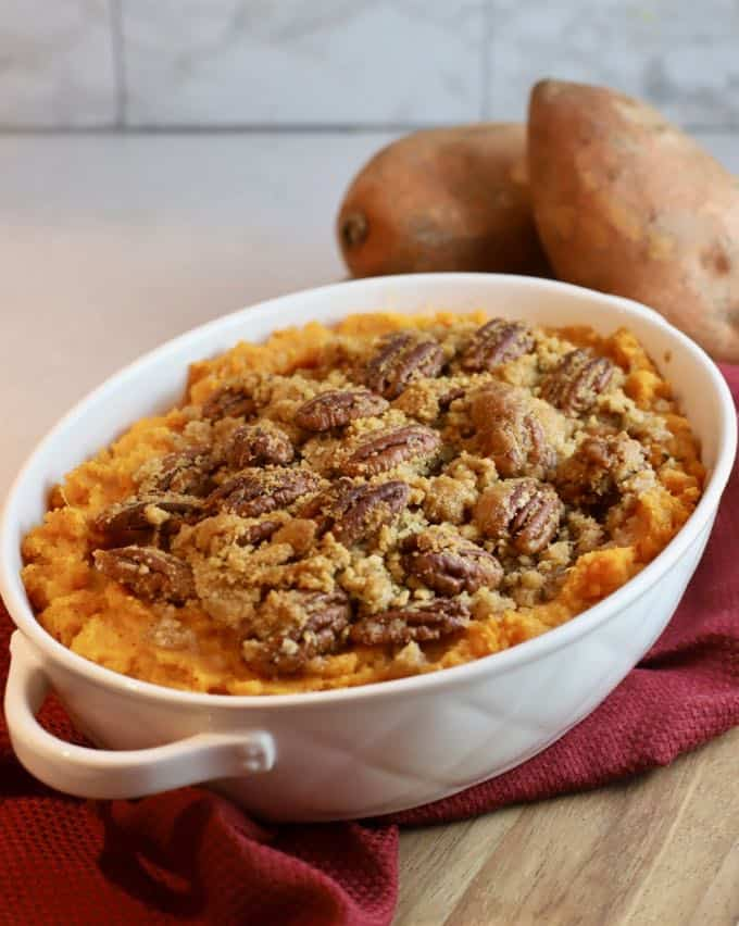 Southern Sweet Potato Casserole in a white baking dish with two raw sweet potatoes in the background.