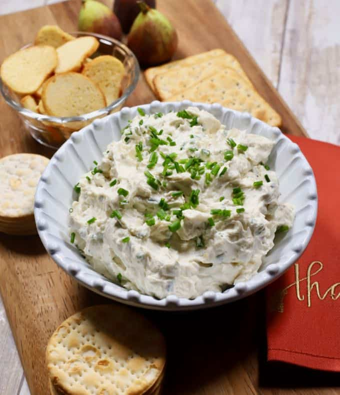 Blue Cheese Spread in a white bowl on a wooden cutting board with assorted crackers.