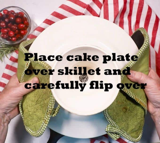 A cake plate on top of a cast iron skillet being flipped over for an upside down cake.