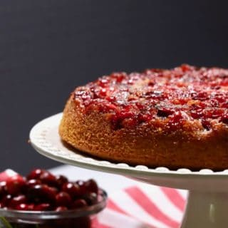 Cranberry Upside Down Cake on a white cake platter with a red and white napkin in the background.