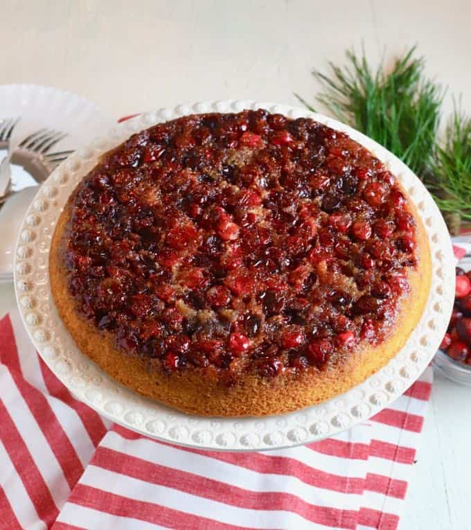 Cranberry Upside Down Cake on a white cake platter on a red and white kitchen towel.