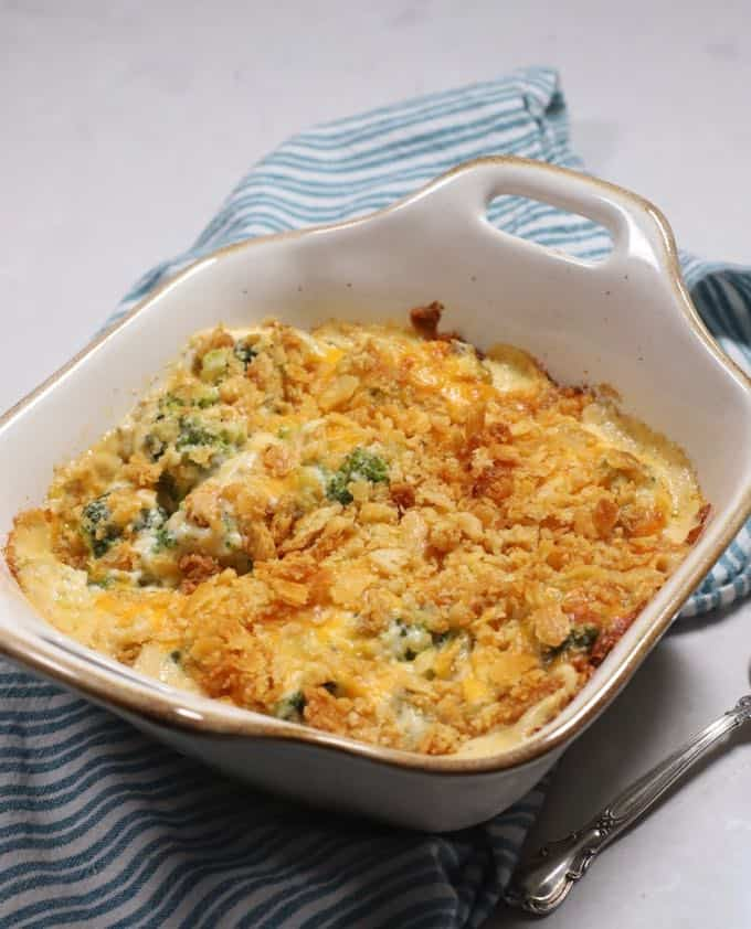 Ultimate broccoli cheese casserole in a white baking dish on a green and white kitchen towel.