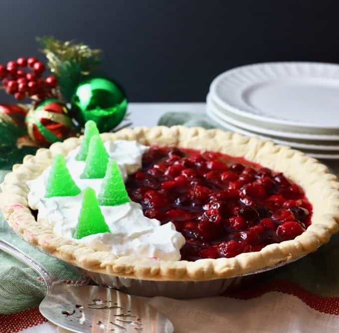 A beautiful cranberry pie on a dessert table with white plates in the background.